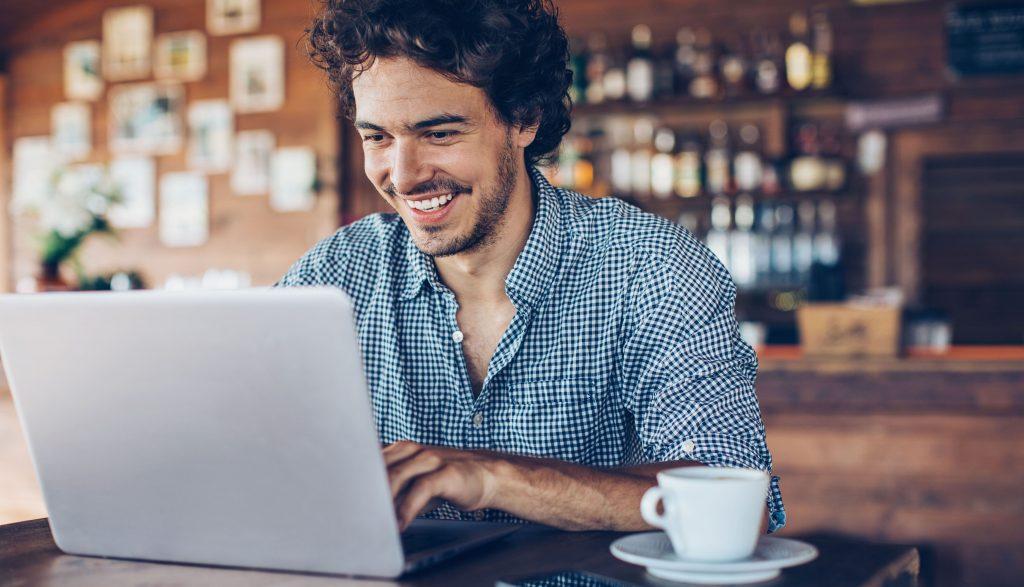 man at laptop in cafe