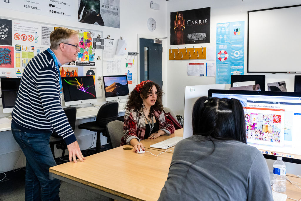 Students with their tutor at mac computers